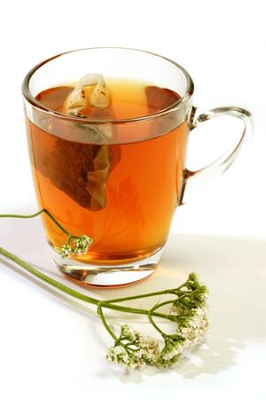 valerian: Tisana in un bicchiere con teabag e la valeriana a sfondo luminoso