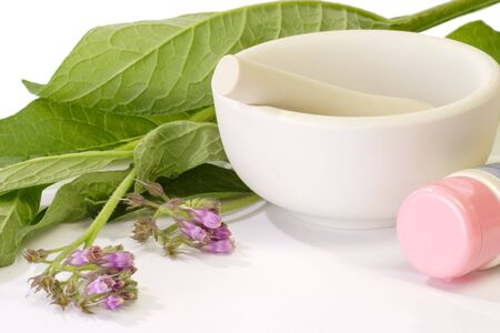 formulation: Comfrey with creme tube and mortar on white background