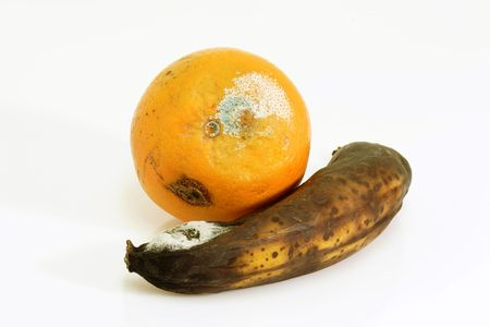 rotten fruit: Mouldy fruits on bright background. Stock Photo