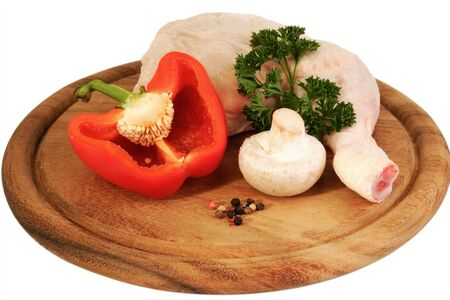 Raw chicken leg with vegetables on bright background photo