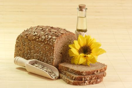 sunflowerseed: Sunflower seeds, sunflower-seed bread and sunflower oil with sunflower blossom Stock Photo
