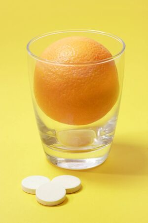 Effervescent tablets with glass and orange on yellow background Stock Photo - 3996145