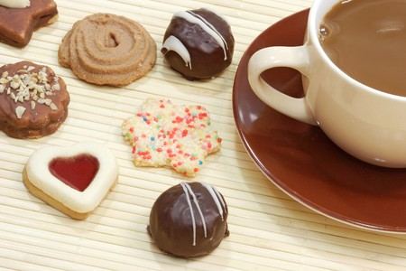 Cup of delicious coffee with cookies on bright background photo