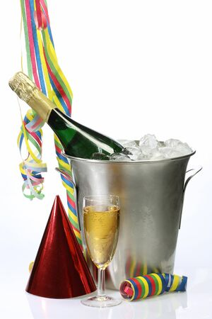 Champagne toast composition with streamers, hat and glass on bright background photo