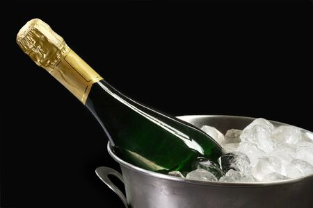 Champagne bottle in a cooler with ice on black background photo