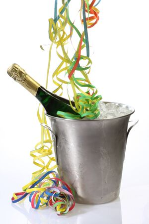 Champaigne bottle in a cooler with ice and streamers on bright background photo