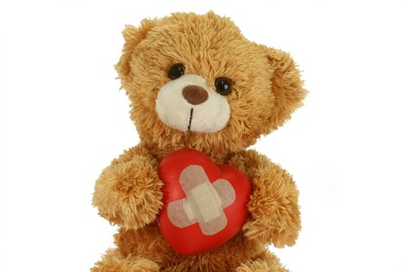 Cute teddy bear with decorative heart on bright background photo