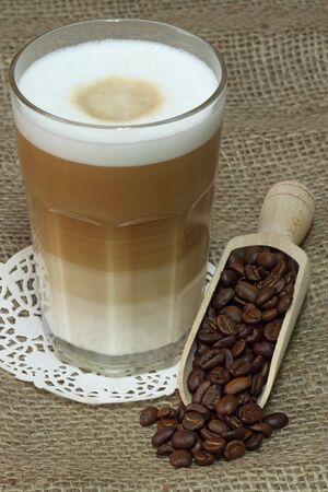macchiato: Latte Macchiato in glass with coffee grain on brown background