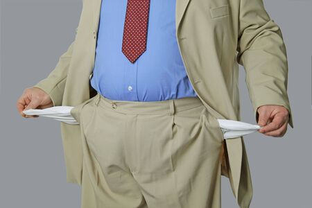 spendthrift: Man shows empty bags on grey background Stock Photo