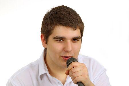 mann: Junger Mann mit Mikrofon auf hellem Hintergrund Stock Photo
