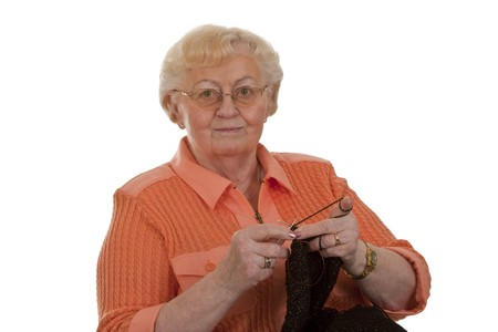 deftness: Old woman senior is knitting-isolated on white background