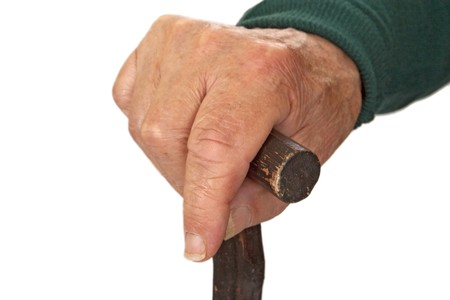Hands of old man with walking stick - detail shot.   Stock Photo