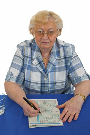 Elderly woman doing sudoku - isolated on white background Stock Photo - 8254280