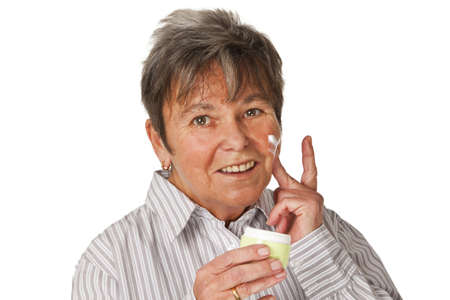 humidify: Senior woman applying lotion on her face isolated on white background