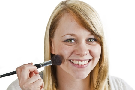 beautify: Attractive young woman applying blusher - isolated on white