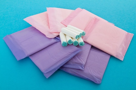 Sanitary napkins and tampons on blue background photo
