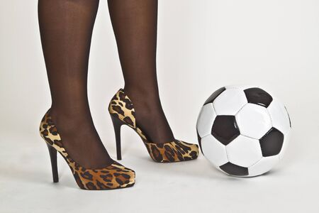 Sexy woman foot with high heels and soccer ball on white background photo
