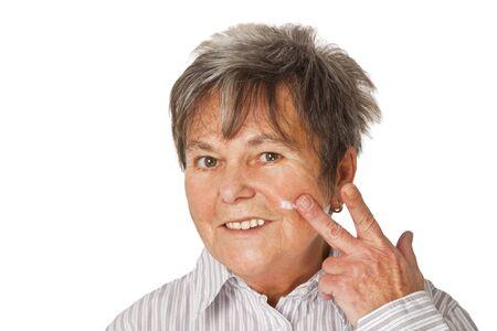 humidify: Female senior applying lotion - isolated on white background Stock Photo