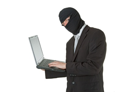 corporate espionage: Man stealing data from a laptop isolated on white background