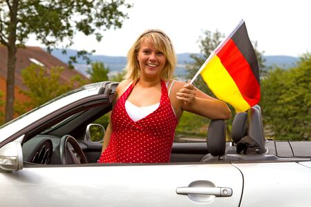 Beautiful woman in open top convertible car with german flag photo