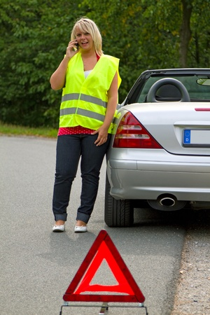 Young woman calling breakdown service. photo