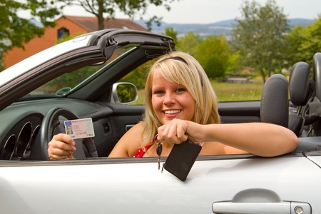Young female showing her car key into the camera photo