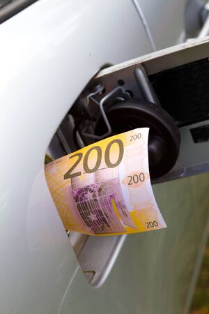Rising gasoline prices concept money in gas tank