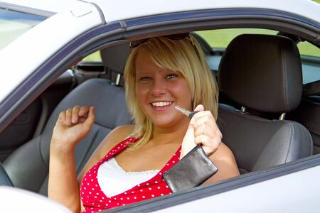 Young female showing her car key into the camera