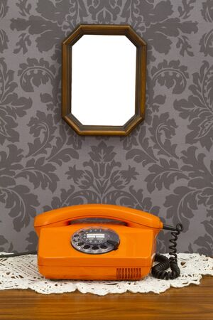 Old fashioned telephone and wooden frame on decorative wallpaper photo