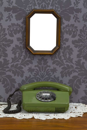 Old fashioned telephone and wooden frame on decorative wallpaper Stock Photo - 14362097