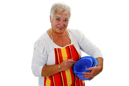 Female senior housewife with bowls and eggbeater - isolated on white background photo