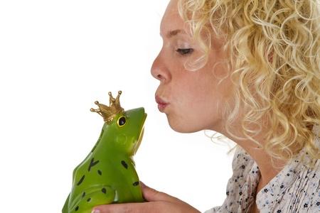 the frog prince: Giovane donna baciare un principe rana isolato su sfondo bianco
