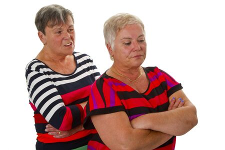 sulk: Two female seniors in dispute - isolated on white background Stock Photo