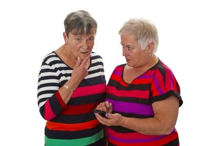 lebensfreude: Zwei weibliche Senior mit Handy auf wei�em Hintergrund isoliert