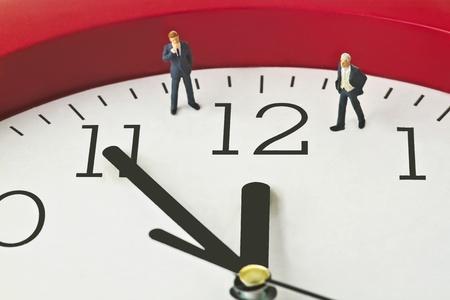 constraints: Figurine on clock face - concept - Five to twelve