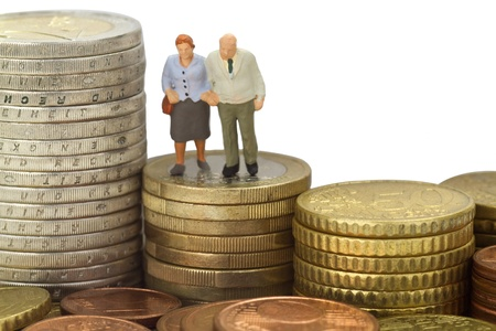 Figurine from senior couple with eruo coins on white background Stock Photo