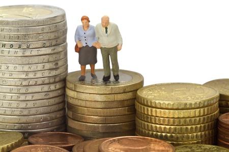 Figurine van senior paar met eruo munten op witte achtergrond Stockfoto