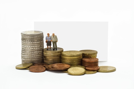 Figurine from senior couple with eruo coins on white background photo