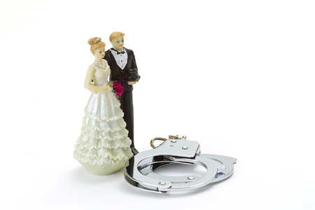 handcuffs woman: Wedding Couple with handcuffs on bright background Stock Photo
