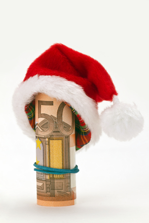 christmas bonus: Santa hat with fifty euro banknote on bright background Stock Photo