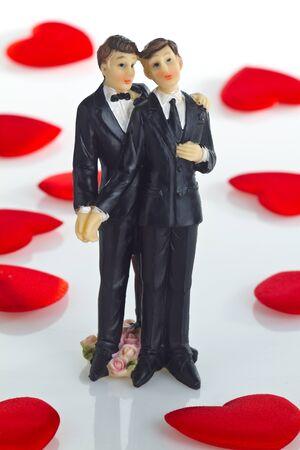 boda gay: Gay Estatuilla de la torta de la boda con pequeños corazones de terciopelo como fondo.