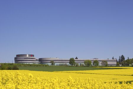 canola: Modern factory building outdoor with canola field