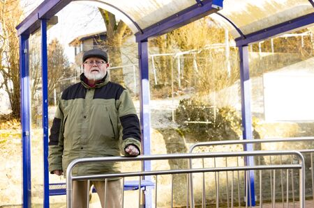 Male senior is waiting on Bus Stop in Winter photo