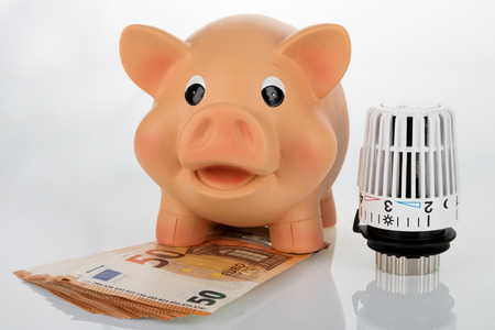 Piggybank with thermostat  on bright background