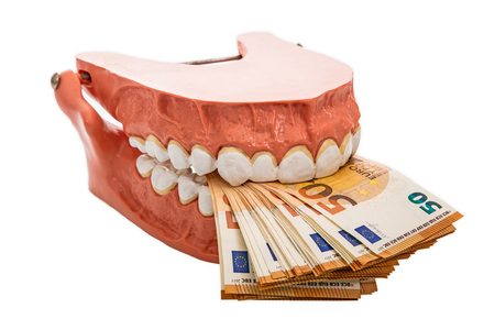 Dentures biting euro banknotes isolated on white background