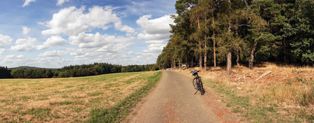 Lone bicycle parked on a rural road overlooking open fields and dense woodland or forests in a panorama landscape