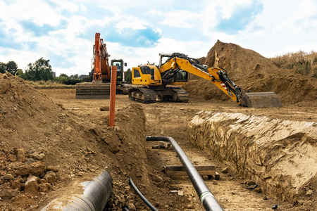 Installation of new gas pipes on a building site with a view down the open trench and heavy duty machinery and digger in the background Stock Photo