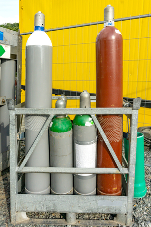 Selection of different gas bottles on a metal stand outdoors on gravel behind a bright yellow structure 版權商用圖片