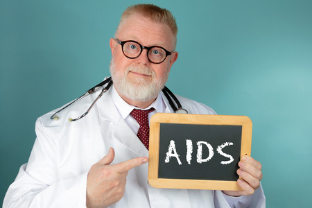 Medical Doctor with eyeglasses holding chalkboard with AIDS lettering on blue background