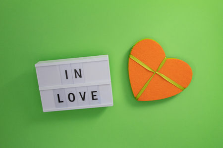 Orange felt heart with ribbon and Lightbox on green cardboard